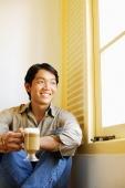 Man sitting next to window holding mug of coffee - Alex Microstock02