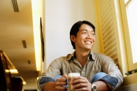 Man sitting, holding mug of coffee, smiling - Alex Microstock02