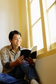 Man sitting, reading book, smiling - Alex Microstock02