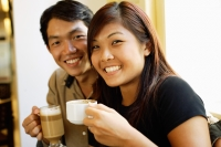 Couple sitting, holding coffee cups, smiling at camera - Alex Microstock02
