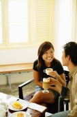 Couple at cafe, holding coffee mugs, food on table - Alex Microstock02