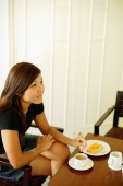 Young woman sitting, food and coffee in front of her, looking away - Alex Microstock02