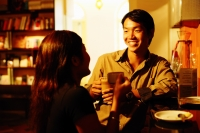 Couple at bar counter, holding coffee cups, talking - Alex Microstock02