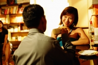 Couple at bar counter, sitting face to face, holding drinks - Alex Microstock02