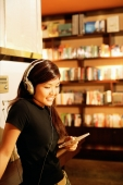 Young woman listening to music, holding CD, smiling - Alex Microstock02