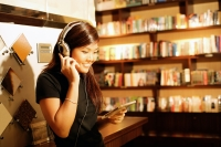 Young woman listening to music, smiling, holding CD - Alex Microstock02
