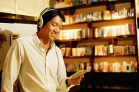 Young man listening to music, smiling, holding CD - Alex Microstock02