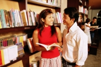 Couple at bookstore, woman holding book, looking at man next to her - Alex Microstock02