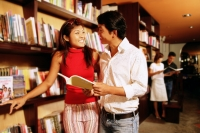 Couple at bookstore, looking each other, man holding book - Alex Microstock02