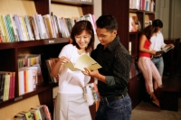 Couple at bookstore, looking at book, people in the background - Alex Microstock02