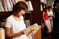 Young woman at bookstore, looking at book - Alex Microstock02