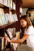 Young woman at bookstore, choosing book from shelf - Alex Microstock02