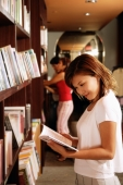 Young woman at bookstore, reading book - Alex Microstock02