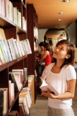 Young woman at bookstore, holding book, looking up - Alex Microstock02