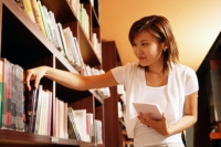 Young woman at bookstore, selecting book from shelf - Alex Microstock02