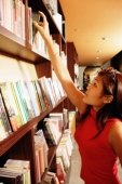 Young woman reaching for book on shelf - Alex Microstock02