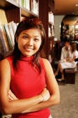 Young woman leaning on book shelf, arms crossed, looking at camera - Alex Microstock02