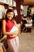 Young woman leaning on book shelf, holding book, looking at camera - Alex Microstock02
