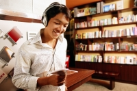 Young man listening to music, smiling, looking down at CD - Alex Microstock02