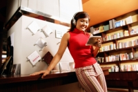 Young woman listening to music, smiling, leaning against counter - Alex Microstock02