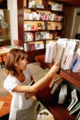 Young woman looking at books on bookshelf, high angle view - Alex Microstock02
