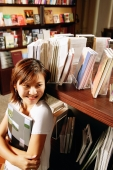 Young woman in bookstore, holding book, looking away - Alex Microstock02