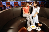 Young women sitting side by side, talking, food on table in front of them - Alex Microstock02