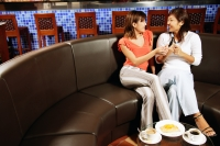 Young women sitting at cafe, one holding mobile phone - Alex Microstock02