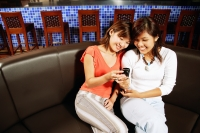 Two women sitting side by side, looking at mobile phone - Alex Microstock02