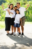 Family standing together, smiling, waving - Alex Microstock02