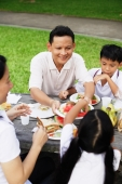 Family sitting at picnic table, father passing daughter food - Alex Microstock02