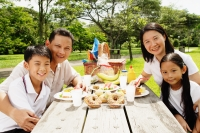 Family sitting at picnic table, looking at camera - Alex Microstock02