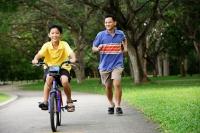 Boy cycling, father running behind him - Alex Microstock02