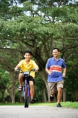 Father and son in park, son cycling, father running alongside him - Alex Microstock02