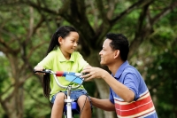 Girl on bicycle, father crouching next to her - Alex Microstock02
