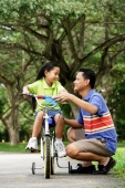 Girl on bicycle, father crouching down next to her - Alex Microstock02