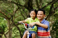 Girl on bicycle, father next to her, both looking at camera - Alex Microstock02