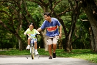 Father and daughter in park, daughter cycling, father running alongside her - Alex Microstock02