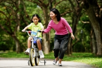 Girl on training bicycle, mother guiding her - Alex Microstock02