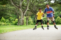 Father and son, in-line skating in park, holding hands - Alex Microstock02
