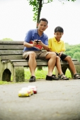 Father and son playing with remote control cars in the park - Alex Microstock02