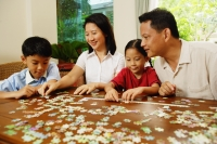Family playing jigsaw puzzle in living room - Alex Microstock02