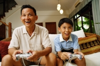Father and son, sitting on sofa, holding video game controllers - Alex Microstock02