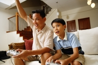 Father and son, sitting on sofa, holding video game controllers, father with arm raised - Alex Microstock02