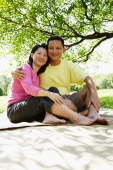 Couple sitting on picnic mat, looking at camera - Alex Microstock02