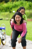 Mother giving daughter a piggyback, looking at camera - Alex Microstock02