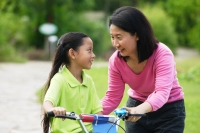 Young girl on bicycle, mother next to her, face to face - Alex Microstock02
