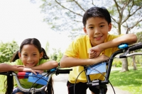 Brother and sister on bicycles, looking at camera - Alex Microstock02