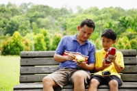 Father and son, sitting on bench, holding remote control cars - Alex Microstock02