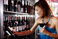 Young woman holding wine glass, looking at wine bottle on shelf - Alex Microstock02